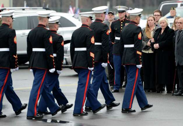 A Marine Corp honor guard passes Mary Morgan, mother of Anthony Denier at the Albany International Airport in Colonie, N.Y. Dec 10, 2012.  (Skip Dickstein/Times Union) Photo: SKIP DICKSTEIN / 00020395A