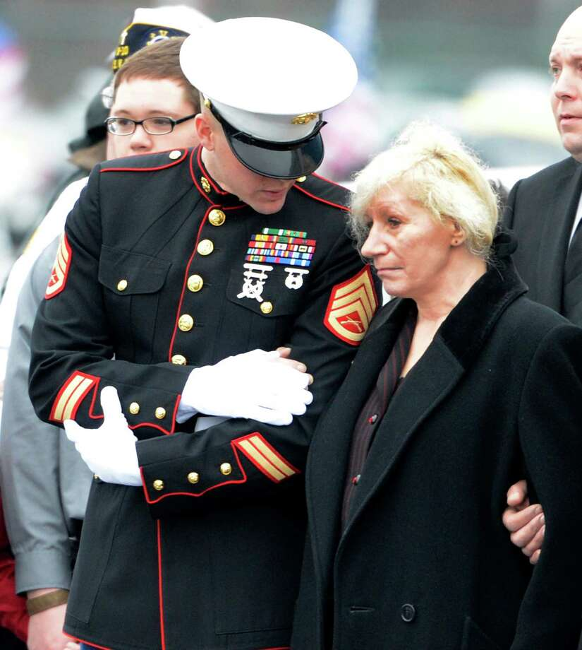 Mary Morgan, mother of the deceased speaks with a Marine Corp representative as the coffin of her son Anthony Denier is taken from the Albany International Airport in Colonie, N.Y. Dec 10, 2012 for a funeral procession to his final resting place.   (Skip Dickstein/Times Union) Photo: SKIP DICKSTEIN / 00020395A