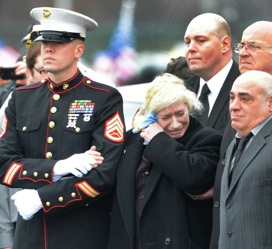 Mary Morgan, center is comforted by a Marine Corp representative as the coffin of Anthony Denier is taken from the Albany International Airport in Colonie, N.Y. Dec 10, 2012 for a funeral procession to his final resting place.   (Skip Dickstein/Times Union) Photo: SKIP DICKSTEIN / 00020395A