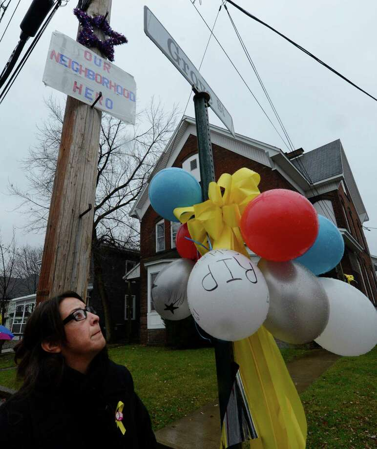 Katrina Dancz fixes balloons on Grove Street in Mechanicville, N.Y. Dec 10, 2012 before the procession of Anthony Denier, her neighbor who was killed in Afghanistan last week came through.   (Skip Dickstein/Times Union) Photo: SKIP DICKSTEIN / 00020395A