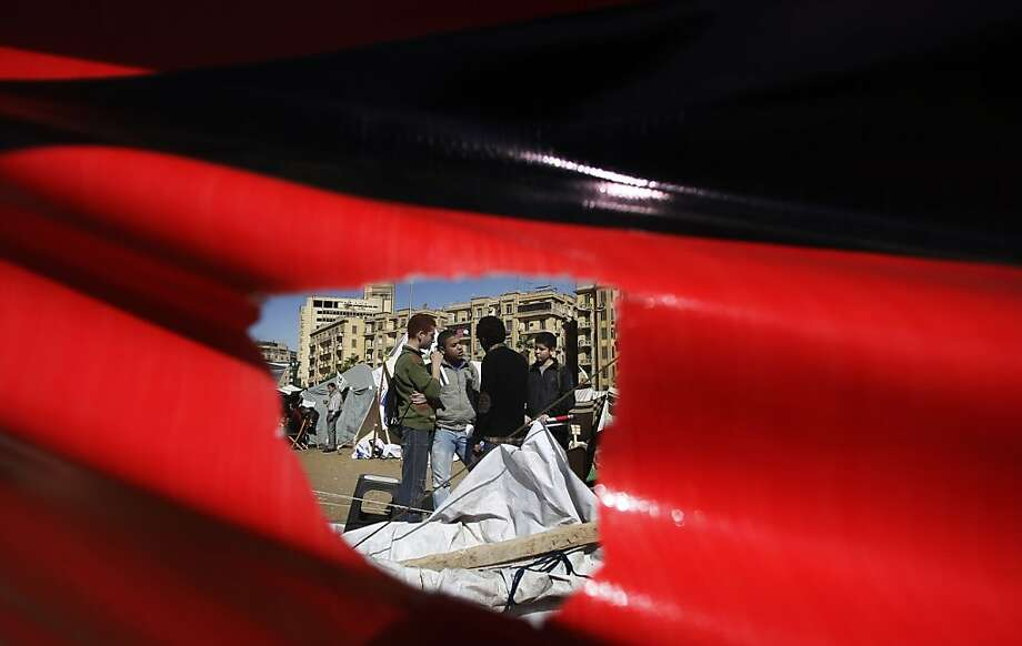 Seen through a hole in a poster,Egyptian boys camp out in Cairo's Tahrir Square. Egypt on Monday gave the military joint responsibility with the police for security and protecting state institutions, allowing the army to arrest civilians. Photo: Petr David Josek, Associated Press