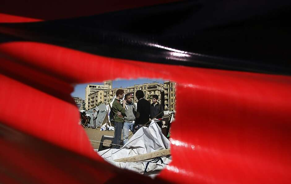 Seen through a hole in a poster, Egyptian boys camp out in Cairo's Tahrir Square. Egypt on Mo