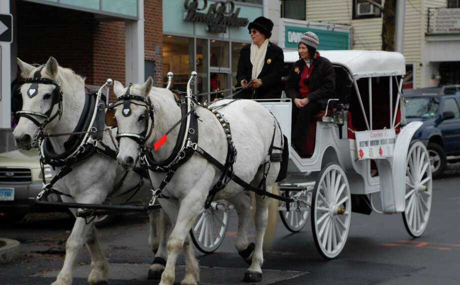 Beth Podhajecki, left, on Main Street with two Clydesdale houses from her Norfolk farm, was joined by friend Nancy Galpin on Saturday to provide free carriage rides, provided during the holiday shopping season by the Downtown Merchants Association. Westport 12/8/12 Photo: Jarret Liotta / Westport News contributed