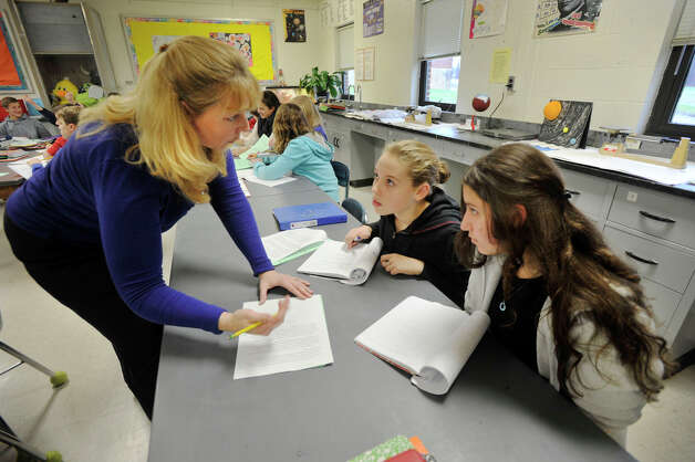 Eighth-grade science teacher Beth Iaciofano, left, helps her students, Haley Dickinson, center, and Christina James during class at Newtown Middle School on Monday, Dec. 10, 2012. The state Department of Education recently released an index of top schools and Newtown Middle School ranked high on the list in the Danbury area. Photo: Jason Rearick / The News-Times