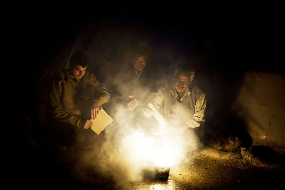 A watched kettle …Syrian men try to boil water at a refugee camp near the Turkish border in Azaz. Photo: Manu Brabo, Associated Press
