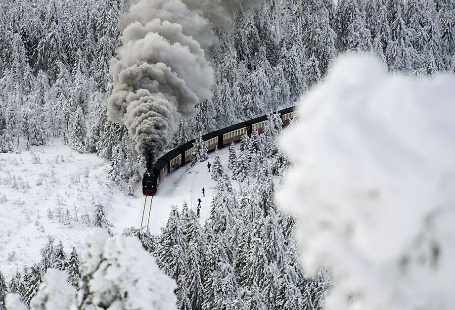 A locomotive pulls a train on a narrow-gauge railroad line in snowbound Wernigerode, Germany. Photo: Jens Schlueter, Associated Press