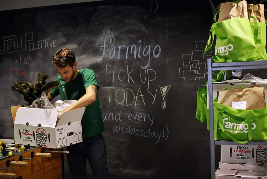 Josh Starkey, an employee at Kiva, checks out his vegetable box after Farmigo delivered fresh produce to his office in San Francisco, Calif., Wednesday, December 5, 2012.  Farmigo is a new startup that partners farmers with companies who want delivery of produce.  Office workers can customize their vegetable box order. Photo: Sarah Rice, Special To The Chronicle