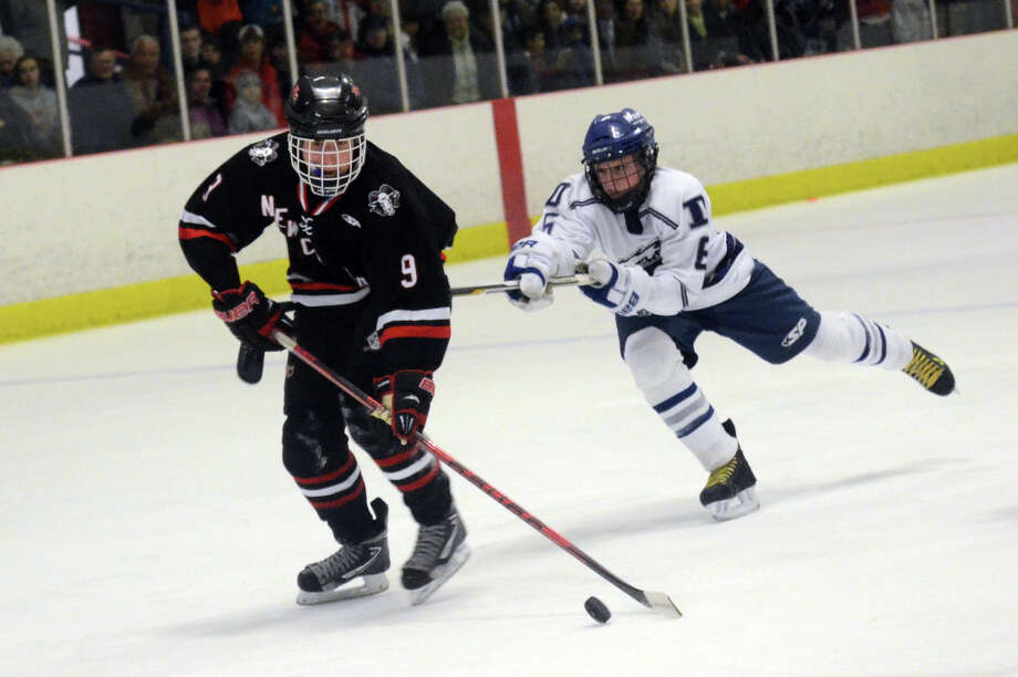 Darien's Nicholas Tuzinkiewicz (6) defends against New Canaan's Peter Reinhardt (9) during the first round of the CIAC boys hockey tournament at Darien Ice Rink on Wednesday, Mar. 7, 2012. Photo: Amy Mortensen