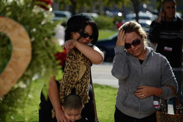 Jenni Rivera fans Michelle Alonzo (L) and her neice Gaby Juarez grieve at a memorial of flowers, candles, ballons and notes to the late Mexican-American singing superstar Jenni Rivera, December 10, 2012 in Burbank, California. Rescue workers searched Monday the wreckage of a plane that carried Rivera, a star on both sides of the border, whose death shocked Latin music fans and celebrities.  AFP PHOTO/ROBYN BECKROBYN BECK/AFP/Getty Images Photo: ROBYN BECK, AFP/Getty Images / AFP