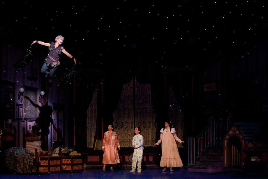 "For the role of Peter Pan, Cathy Rigby is able to fly above the stage through an elaborate system of cables. Cade Cannon Ball, Julia Massey and Krista Buccellato play the Darling children in ""Peter Pan."""