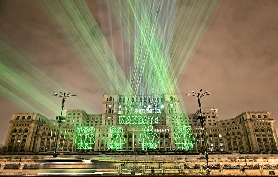 Lasers project the number of seats won in the parliamentary elections by the political groups that received over the minimum 5 percent of the votes, on the facade of the communist era built Palace of Parliament in Bucharest, Romania, Monday night, Dec. 10, 2012. Partial results show Romania's ruling center-left alliance Social Liberal Union won about 59 percent of the seats in the 452-seat legislature, followed by a center-right group allied to President Traian Basescu that polled just below 17 percent. A populist party lead by a media tycoon scored about 14 percent in Sunday's election and an ethnic Hungarian party won just over 5 percent. (AP Photo/Vadim Ghirda) Photo: Vadim Ghirda, Associated Press