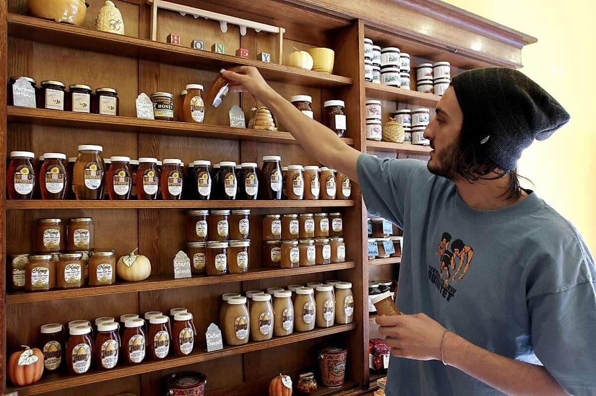 Shop Keeper, Christian Riechert restocks the honey wall at Her Majesty's Secret Beekeeper shop in San Francisco, Calif. Calif. on Saturday Dec. 8, 2012.