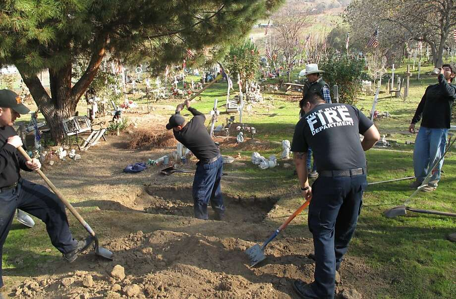 "Members of the Tule River Indian Reservation Fire Department help to dig the grave Monday Dec. 10, 2012 of a tribal member who died recently of natural causes. Afterward, they said they would move to the other side of the colorfully decorated cemetery for the somber task of digging a grave for 8-year-old Alyssa Celaya, who was murdered along with her grandmother and two other relatives on Sunday. Her father, 31-year-old Hector Celaya, is suspected in the killings and died in a shootout with Tulare County sheriff's deputies. The men said that they dig graves by hand instead of using backhoes or other machinery ""out of respect."" But never have they had to dig so many at once. All told, 5 residents of the reservation are dead. (AP Photo/Tracie Cone) Photo: Tracie Cone, Associated Press"