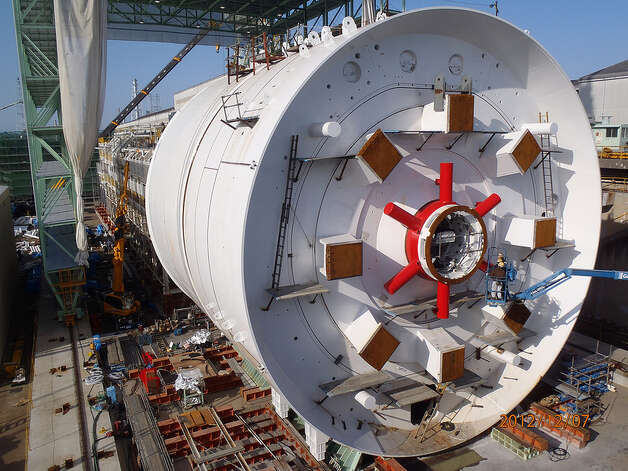 Crews in Japan prepare the SR 99 tunnel boring machine for cutterhead installation in fall 2012. This area directly behind the cutterhead is the machine's mixing chamber. The red spokes at the center work like a blender, mixing the excavated material into a consistency that can be easily removed by the machine's screw conveyor belt. Photo: Washington State Department Of Transportation