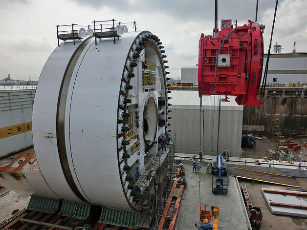Crews in Japan hoist the SR 99 tunnel boring machine's brightly painted segment erector into place in summer 2012. The segment erector is the part of the machine that will install the curved concrete segments that form the tunnel's walls. Photo: Washington State Department Of Transportation