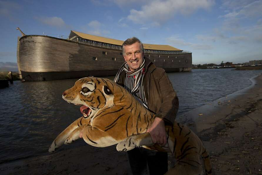 Johan Huibers poses with a stuffed tiger in front of the full scale replica of Noah's Ark after bein
