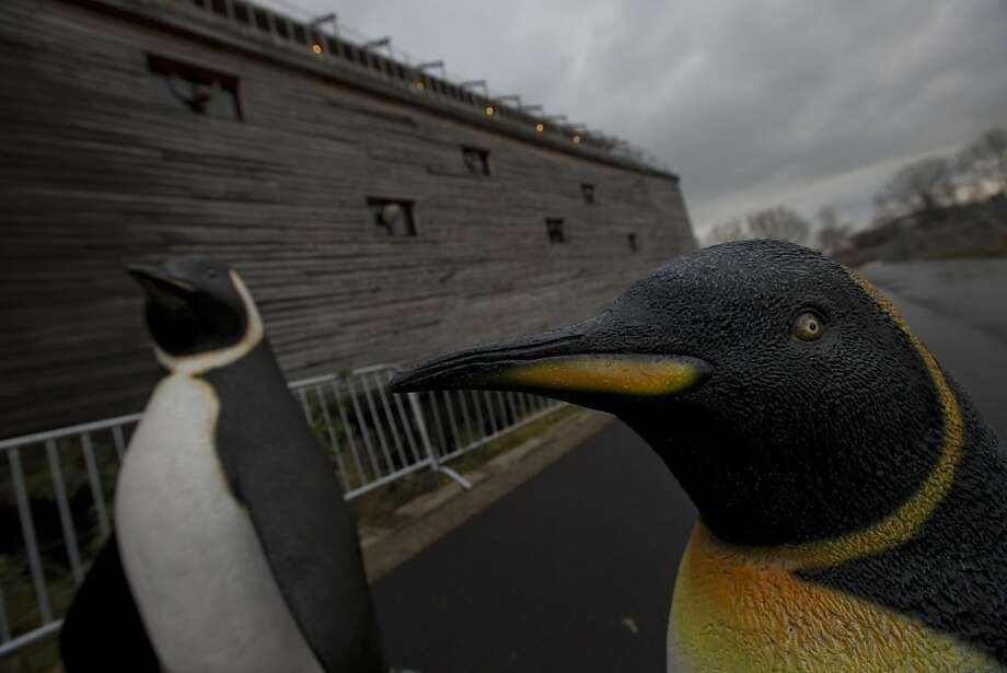 Life-seize replica's of penguins are seen outside a full scale replica of Noah's Ark which has opened its doors in Doredrecth, Netherlands, Monday Dec. 10, 2012, after receiving permission to host up to 3,000 visitors per day. Stormy weather could do nothing to dampen the good mood of its creator, Dutchman Johan Huibers: in fact, the rain was appropriate. For those who don't know or remember the Biblical story, God ordered Noah to build a boat massive enough to save animals and humanity while God destroyed the rest of the earth in an enormous flood. (AP Photo/Peter Dejong) Photo: Peter Dejong, Associated Press