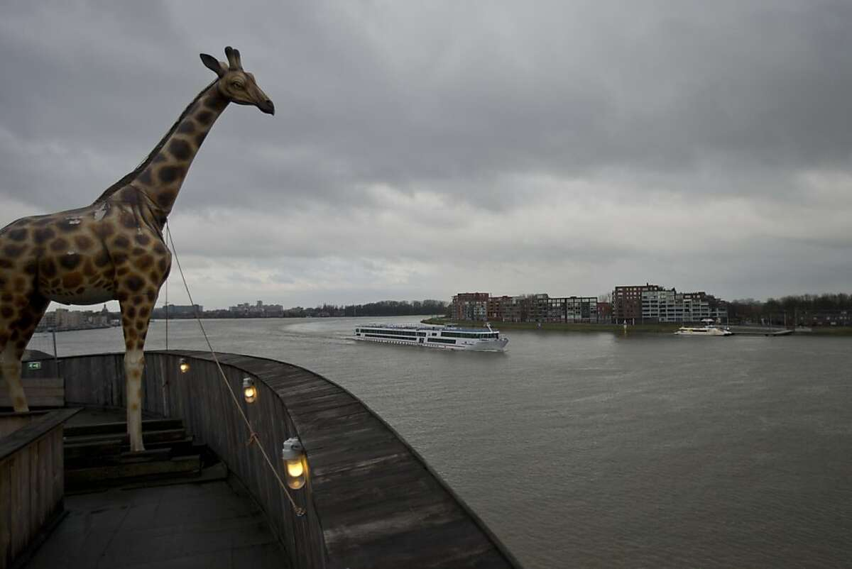 A life-size replica of a giraffe overlooks Merwede river from a full scale replica of Noah's Ark which opened its doors in Dordrecht, Netherlands, Monday Dec. 10, 2012, after receiving permission to receive up to 3,000 visitors per day. Stormy weather could do nothing to dampen the good mood of its creator, Dutchman Johan Huibers: in fact, the rain was appropriate. For those who don't know or remember the Biblical story, God ordered Noah to build a boat massive enough to save animals and humanity while God destroyed the rest of the earth in an enormous flood. (AP Photo/Peter Dejong)