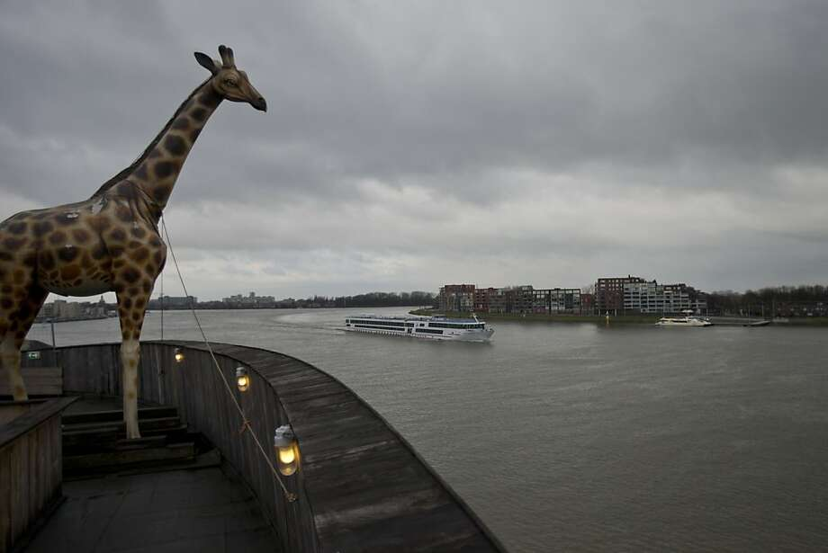 A life-size replica of a giraffe overlooks Merwede river from a full scale replica of Noah's Ark which opened its doors in Dordrecht, Netherlands, Monday Dec. 10, 2012, after receiving permission to receive up to 3,000 visitors per day. Stormy weather could do nothing to dampen the good mood of its creator, Dutchman Johan Huibers: in fact, the rain was appropriate. For those who don't know or remember the Biblical story, God ordered Noah to build a boat massive enough to save animals and humanity while God destroyed the rest of the earth in an enormous flood. (AP Photo/Peter Dejong) Photo: Peter Dejong, Associated Press