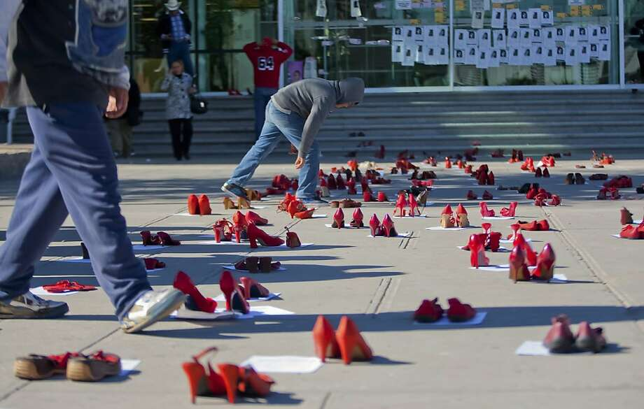 People walk past hundreds of red shoes symbolizing missing women in front of the State Attorney Office during a demo in Ciudad Juarez, Mexico, on December 10, 2012. Relatives of missing women protested in Ciudad Juarez for the lack of progress in the investigations of the crimes. AFP PHOTO/JESUS ALCAZARJesus Alcazar/AFP/Getty Images Photo: Jesus Alcazar, AFP/Getty Images