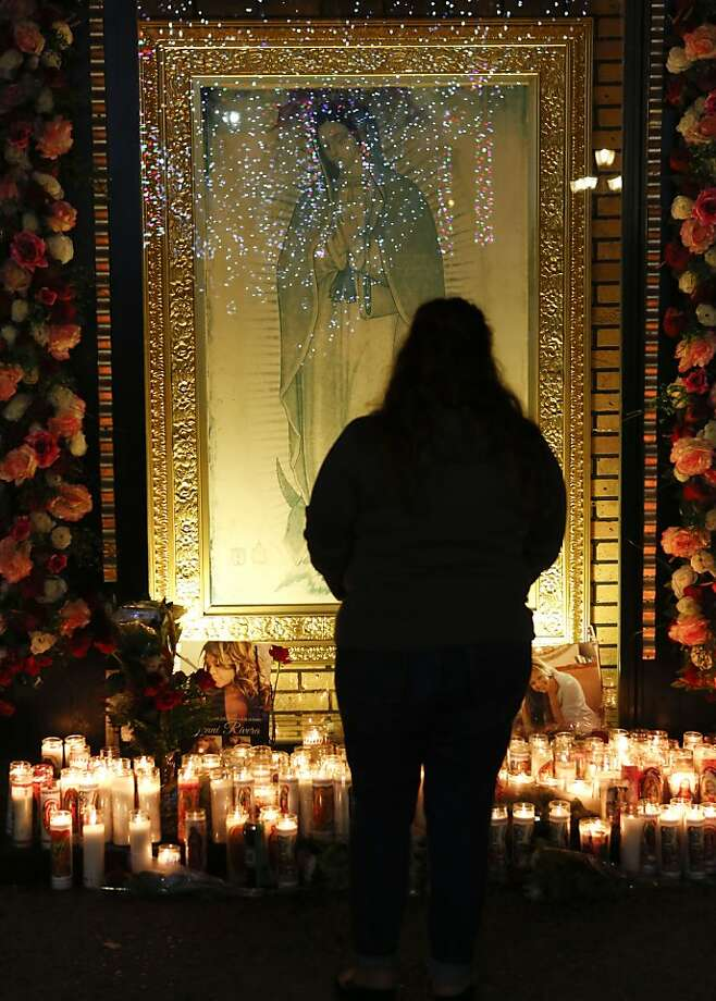 Fan Jenny Guerrero pays tribute to singer Jenni Rivera at a makeshift memorial in front of an image of the Virgin of Guadalupe at the Plaza Mexico shopping center in Lynwood, Calif., early Monday, Dec. 10, 2012. Authorities have not confirmed her death, but Rivera's relatives in the U.S. say they have few doubts that she was on the Learjet 25 that disintegrated on impact Sunday in rugged territory in Nuevo Leon state in northern Mexico. (AP Photo/Patrick T. Fallon) Photo: Patrick T. Fallon, Associated Press