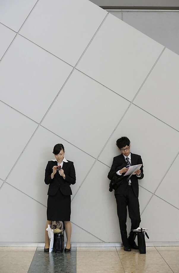 University students use smartphones at a job fair hosted by Mynavi Corp. in Tokyo, Japan, on Saturday, Dec. 8, 2012. In Japan, many students accept job offers from large companies six months before graduating and may stay with the same employer until retirement, said Yoshihide Suzuki, an administrative director at the career center at Waseda University. Photographer: Akio Kon/Bloomberg Photo: Akio Kon, Bloomberg