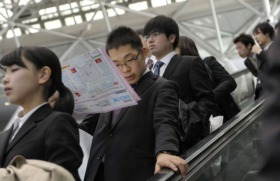 University students ride an escalator at a job fair hosted by Mynavi Corp. in Tokyo, Japan, on Saturday, Dec. 8, 2012. In Japan, many students accept job offers from large companies six months before graduating and may stay with the same employer until retirement, said Yoshihide Suzuki, an administrative director at the career center at Waseda University. Photographer: Akio Kon/Bloomberg Photo: Akio Kon, Bloomberg