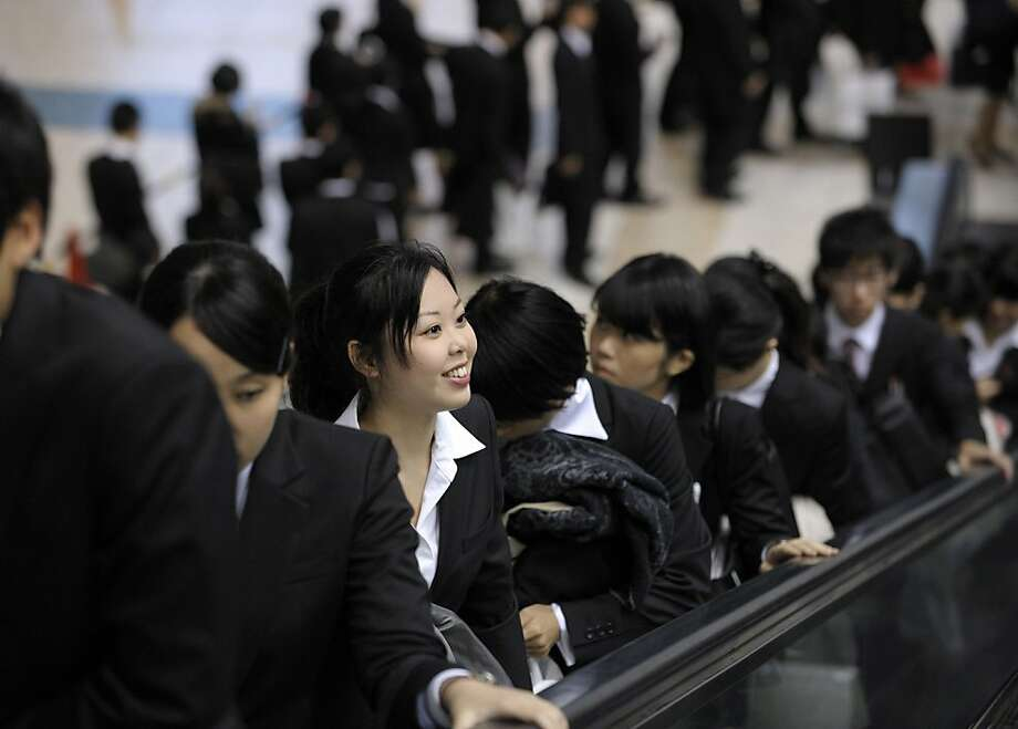 University students ride on an escalator at a job fair hosted by Mynavi Corp. in Tokyo, Japan, on Saturday, Dec. 8, 2012. In Japan, many students accept job offers from large companies six months before graduating and may stay with the same employer until retirement, said Yoshihide Suzuki, an administrative director at the career center at Waseda University. Photographer: Akio Kon/Bloomberg Photo: Akio Kon, Bloomberg