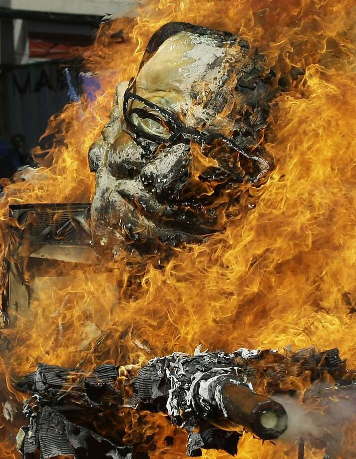 Protesters burn an effigy of Philippine President Benigno Aquino III on a mock tank as they commemorate International Human Rights Day near the Presidential Palace in Manila, Philippines, on Monday Dec. 10, 2012. The group called the Aquino administration as alleged human rights violators. (AP Photo/Aaron Favila) Photo: Aaron Favila, Associated Press