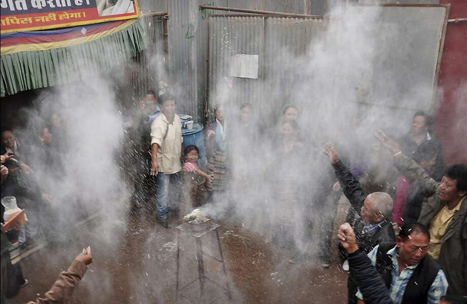 Exiled Tibetans throw tsampa, or barley flour, in the air during a small ceremony to celebrate the anniversary of Tibetan spiritual leader the Dalai Lama's Nobel Prize and to mark World Human Rights Day in Bikaner, Rajasthan, India, Monday, Dec.10, 2012. The Dalai Lama was awarded the Nobel Peace Prize in 1989. (AP Photo/Dinesh Gupta) Photo: Dinesh Gupta, Associated Press
