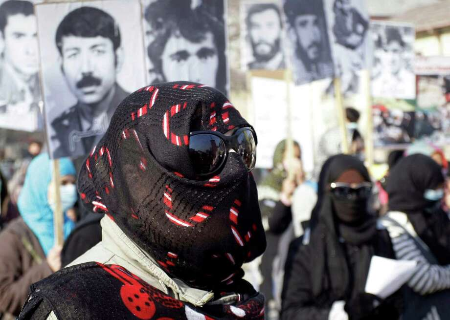 Concealing her identity, a woman marches as others hold photos of loved ones who have been killed in the past three decades of war and related violence during a demonstration for human rights in Kabul, Afghanistan, on Monday. Photo: Musadeq Sadeq, STF / AP