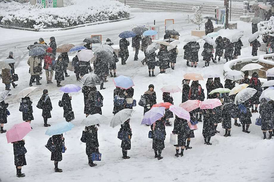 Students make lines on a bus terminal covered by snow to wait for transportation in Nagano City in the morning on December 10, 2012.  Heavy snow hit wide areas of Japan on December 10 due to cold air that brought a winter pressure system.    AFP PHOTO / KAZUHIRO NOGIKAZUHIRO NOGI/AFP/Getty Images Photo: Kazuhiro Nogi, AFP/Getty Images