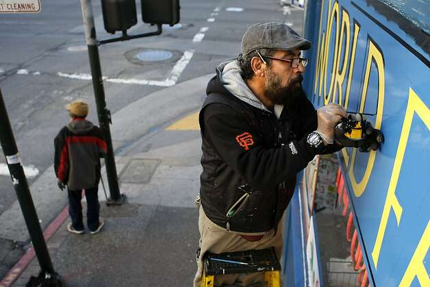 Wilfredo Leyva, 53, a sign painter since moving to S.F. from Nicaragua 35 years ago, puts the finishing touches on a window at Tommy's Joynt. Photo: Sean Havey, The Chronicle