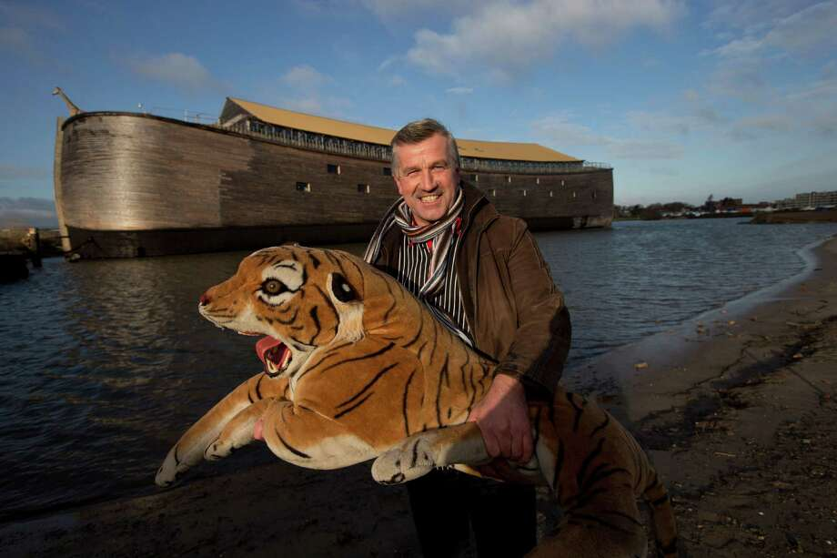 Johan Huibers poses with a stuffed tiger in front of the full scale replica of Noah's Ark after being asked by a photographer to go outside with the animal in Dordrecht, Netherlands, Monday Dec. 10, 2012. The Ark has opened its doors in the Netherlands after receiving permission to receive up to 3,000 visitors per day. For those who don't know or remember the Biblical story, God ordered Noah to build a boat massive enough to save animals and humanity while God destroyed the rest of the earth in an enormous flood. (AP Photo/Peter Dejong) Photo: Peter Dejong, Associated Press / AP