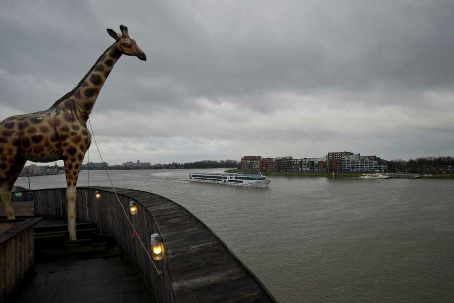 A life-size replica of a giraffe overlooks Merwede river from a full scale replica of Noah's Ark which opened its doors in Dordrecht, Netherlands, Monday Dec. 10, 2012, after receiving permission to receive up to 3,000 visitors per day. Stormy weather could do nothing to dampen the good mood of its creator, Dutchman Johan Huibers: in fact, the rain was appropriate. For those who don't know or remember the Biblical story, God ordered Noah to build a boat massive enough to save animals and humanity while God destroyed the rest of the earth in an enormous flood. (AP Photo/Peter Dejong) Photo: Peter Dejong, Associated Press / AP