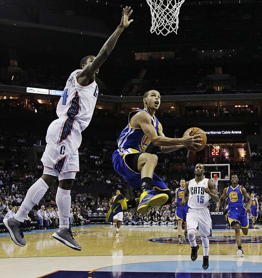 Stephen Curry navigates an opening to the basket around Charlotte's Michael Kidd-Gilchrist (left). Photo: Chuck Burton, Associated Press