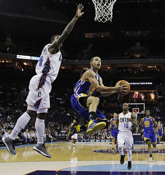 Stephen Curry navigates an opening to the basket around Charlotte's Michael Kidd-Gilchrist (left).