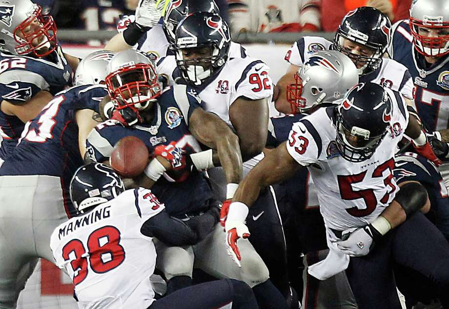 Patriots running back Stevan Ridley (22) fumbles as Texans free safety Danieal Manning (38), nose tackle Earl Mitchell (92) and inside linebacker Bradie James (53) defend during the first quarter. Photo: Brett Coomer, Houston Chronicle / © 2012  Houston Chronicle