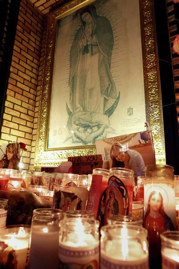 Candles and pictures are displayed in tribute to singer Jenni Rivera in front of an image of the Virgin of Guadalupe at the Plaza Mexico shopping center in Lynwood, Calif., on Sunday, Dec. 9, 2012. Authorities have not confirmed her death, but Rivera's relatives in the U.S. say they have few doubts that she was on the Learjet 25 that disintegrated on impact Sunday in rugged territory in Nuevo Leon state in northern Mexico. (AP Photo/Patrick T. Fallon) Photo: Patrick T. Fallon, Associated Press / FR160581 AP