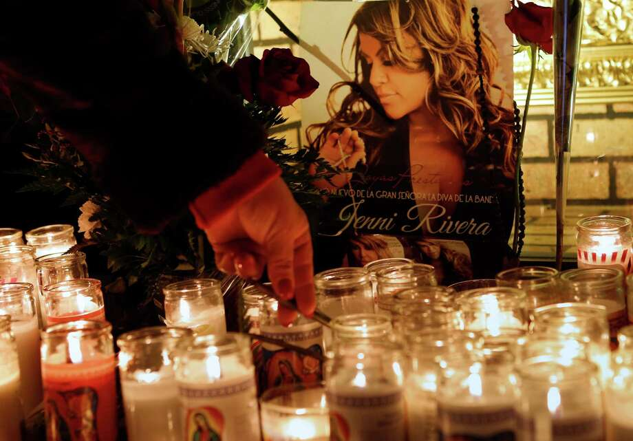 A woman adjusts a flower in front of candles and pictures displayed in tribute to singer Jenni Rivera at the Plaza Mexico shopping center in Lynwood, Calif., early Monday, Dec. 10, 2012. Authorities have not confirmed her death, but Rivera's relatives in the U.S. say they have few doubts that she was on the Learjet 25 that disintegrated on impact Sunday in rugged territory in Nuevo Leon state in northern Mexico. (AP Photo/Patrick T. Fallon) Photo: Patrick T. Fallon, Associated Press / FR160581 AP