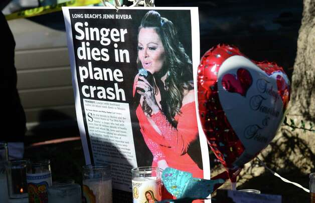 Candles are placed at a makeshift shrine mourning the death of Mexican-American diva Jenni Rivera in front of her home in Lakewood, California on December 10, 2012, south of Los Angeles. Fans and celebrities are mourning the death of Rivera, a star on both sides of the border, as investigators scoured the site of her plane wreck for clues. The 43-year-old singer was among seven people, including two pilots, killed when their small Learjet plane crashed in rugged terrain in the northern Mexican state of Nuevo Leon early December 9. AFP PHOTO / Frederic J. BROWNFREDERIC J. BROWN/AFP/Getty Images Photo: FREDERIC J. BROWN, AFP/Getty Images / AFP