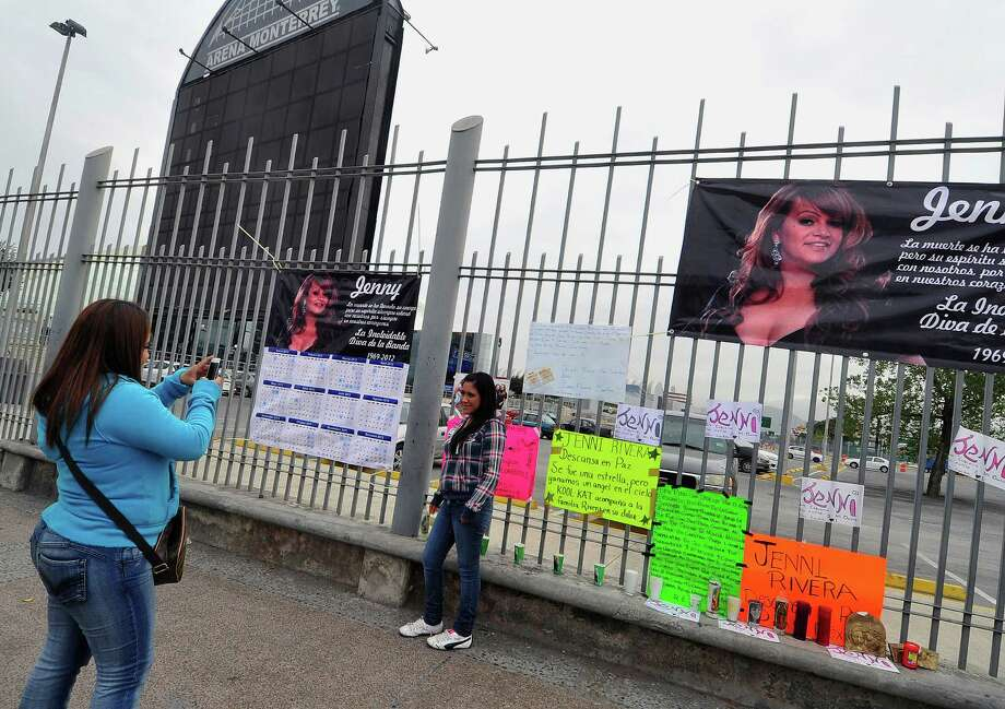 Two fans of Mexican-US singer Jenni Rivera take pictures outside the Arena Monterrey, where she performed her last show, in Monterrey, Nuevo Leon state, Mexico on December 10, 2012. The wreckage of a plane carrying Rivera was found in northern Mexico and there were no survivors, officials said. The Lear Jet was flying from Monterrey to Toluca, and was carrying six other people besides the singer, said Iturbide's Mayor Antonio Gonzalez. AFP PHOTO /STRSTR/AFP/Getty Images Photo: STR, AFP/Getty Images / AFP
