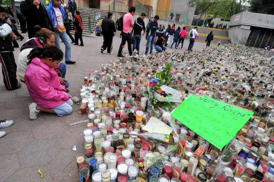 Fans of Mexican-US singer Jenni Rivera remain next to hundreds of candles outside the Arena Monterrey, where she performed her last show, in Monterrey, Nuevo Leon state, Mexico on December 10, 2012. The wreckage of a plane carrying Rivera was found in northern Mexico and there were no survivors, officials said. The Lear Jet was flying from Monterrey to Toluca, and was carrying six other people besides the singer, said Iturbide's Mayor Antonio Gonzalez. AFP PHOTO /STRSTR/AFP/Getty Images Photo: STR, AFP/Getty Images / AFP