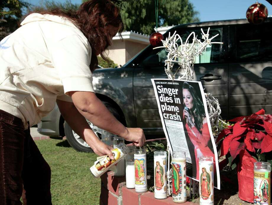 A fan lights a candle outside the home of singer Jenni Rivera's mother in Lakewood, Calif. Monday, Dec. 10, 2012. Rivera died Sunday in a plane crash in Mexico. U.S. authorities confirmed Monday that Jenni Rivera, a U.S.-born singer whose soulful voice and openness about her personal troubles made her a Mexican-American superstar, was killed Sunday in a plane crash in northern Mexico. (AP Photo/Jason Redmond) Photo: Jason Redmond, Associated Press / FR74394 AP