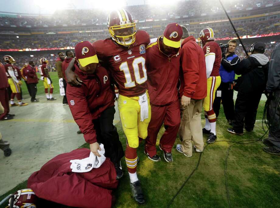 Washington Redskins quarterback Robert Griffin III is helped off the field after an injury during the second half of an NFL football game against the Baltimore Ravens in Landover, Md., Sunday, Dec. 9, 2012. Griffin suffered a sprained knee at the end of a 13-yard scramble. The Redskins won 31-28. (AP Photo/Patrick Semansky) Photo: Patrick Semansky