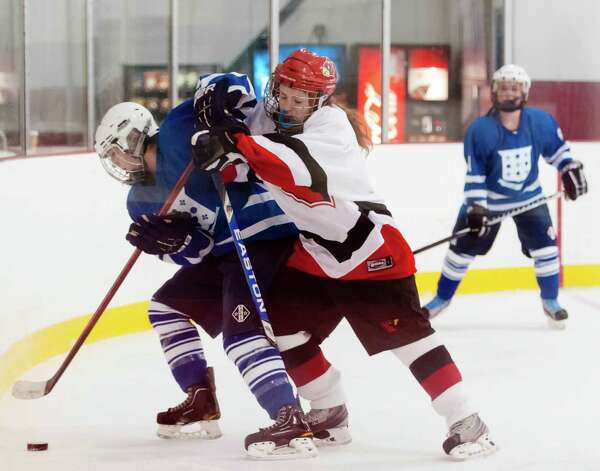Greenwich high school's Sara Schectman and Portledge school's Lindsay Miller battle for the puck in a girls ice hockey game played at Dorothy Hamill ice rink, Greenwich CT Monday December 10th 2012. Photo: Mark Conrad / Stamford Advocate Freelance
