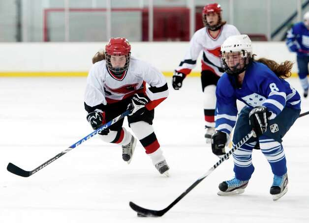 Greenwich high school's Sara Schectman tries to catch up to Portledge school's Holly Ackermann in a girls ice hockey game played at Dorothy Hamill ice rink, Greenwich CT Monday December 10th 2012. Photo: Mark Conrad / Stamford Advocate Freelance