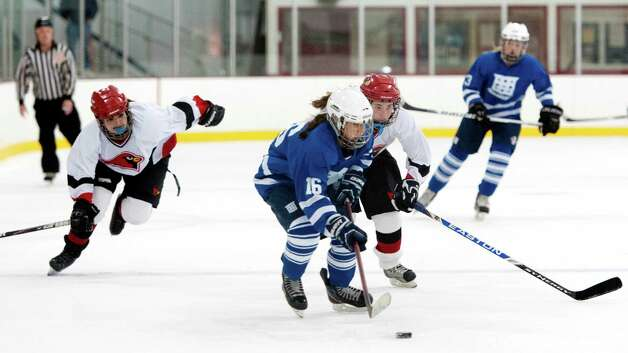 Greenwich high school's Ciel McDermid and Sara Schectman go after Portledge school's Julianne Mauriello in a girls ice hockey game played at Dorothy Hamill ice rink, Greenwich CT Monday December 10th 2012. Photo: Mark Conrad / Stamford Advocate Freelance
