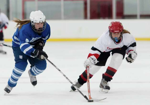 Portledge school's Georgia Keogh and Greenwich high school's Maddy Graves fight for the puck in a  girls ice hockey played at Dorothy Hamill ice rink, Greenwich CT Monday December 10th 2012. Photo: Mark Conrad / Stamford Advocate Freelance