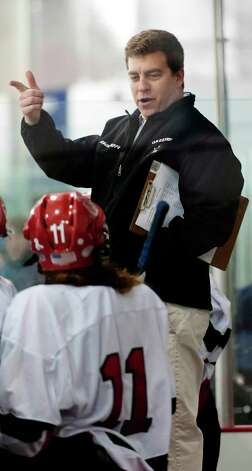 Greenwich high school girls ice hockey team head coach Brett Farson gives instruction to one of his players during a game against Portledge school played at Dorothy Hamill ice rink, Greenwich CT Monday December 10th 2012. Photo: Mark Conrad / Stamford Advocate Freelance